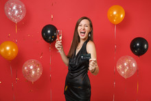 Overjoyed Young Woman In Little Black Dress Screaming Celebrating, Holding Credit Card Glass Of Champagne On Bright Red Background Air Balloons. Happy New Year, Birthday Mockup Holiday Party Concept.