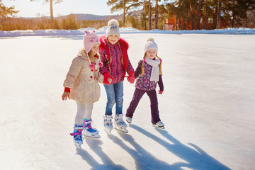 Fototapeta Three little girls skate on the ice. Vacations and holidays in nature