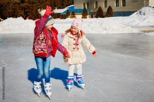 Foto op Canvas Wintersporten Little girls learn to skate. They are laughing and happy. Concept of friendship and fun holidays.