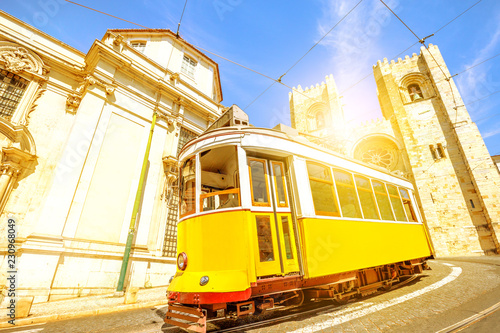 Historic yellow tram line in front of Lisbon Cathedral in Alfama district, Lisbon, Portugal. Lisbon street with typical vintage tram and Se de Lisboa. Sunset light shot.