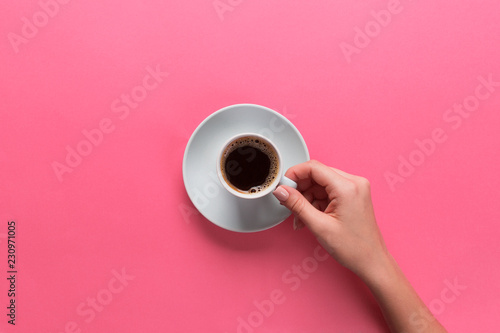 Fotografía  Minimalistic style woman hand holding a cup of coffee on pink background