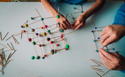 Fotografia  teacher and child making geometric shapes from sticks and play dough
