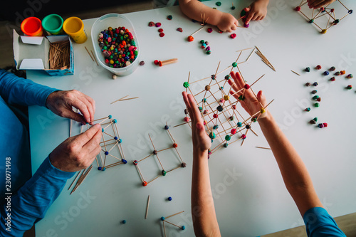 teacher and kids making geometric shapes from sticks and play dough