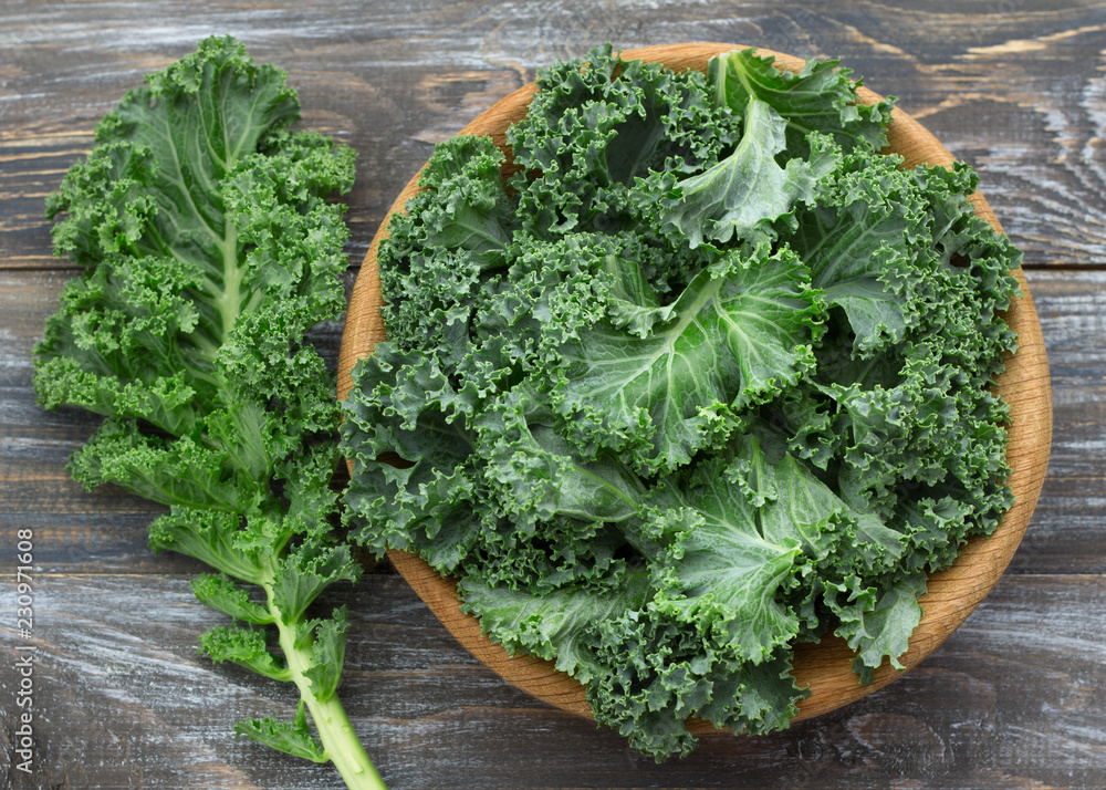Fototapeta Fresh green curly kale leaves on a wooden table. selective focus. rustic style. healthy vegetarian food