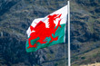 Welsh flag waving in the beautiful landscape of Llanberis, Snowdonia in Wales at the lake padarn