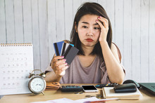 Stress Asian Woman Looking At Credit Cards In Hand No Money For Debt With Deadline Calendar On Desk
