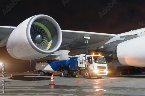 Large aircraft jet engines, Fueling a huge airplane, a truck with fuel with hoses connected to a fuel tank Canvas Print