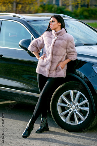 Fotografie, Tablou  A beautiful brunette in a light fur coat and black trousers is standing near the