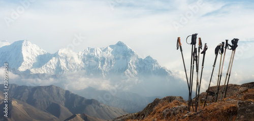 Fototapeta Trekking sticks on background mountains range. Panoramic view. obraz