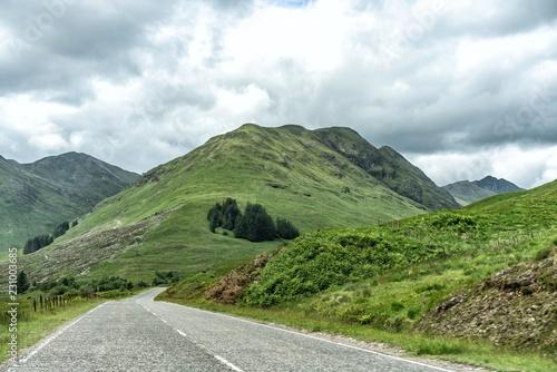 Fotobehang Wit Verlassene Straße führt in Richtung grünbewachsenen hohen Hügel bei mystischer Atmosphäre in Schottland