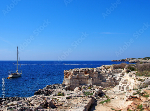 In de dag Kust a coastal scene with a yacht in a bright blue sunlit Mediterranean sea near ciutadella menorca with cliffs surrounding the bay and buildings in the distance