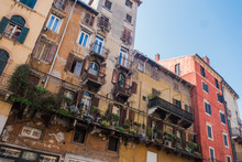 Beautiful Traditional Italian Building With Flowers On Balcony Of Medieval Wall, Piazza Delle Erbe, Verona, Italy