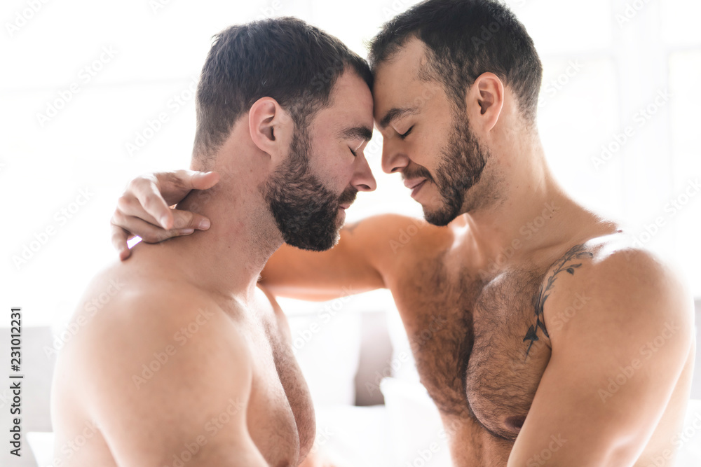 Fototapeta A Handsome gay men couple on bed together