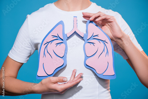 Obraz partial view of woman in white tshirt with paper crafted lungs on blue backdrop - fototapety do salonu