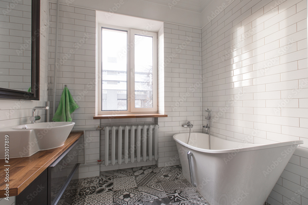 Fototapeta White beautiful attic bathroom in pastel gray and nude colours, with spectacular oval bath