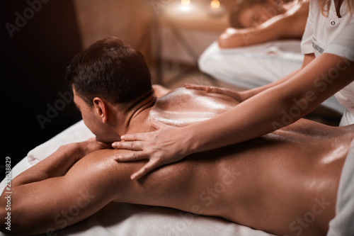 Valokuva  Handsome caucasian businessman and his beautiful wife treating themselves to a comforting back massage, a gentle relaxing massage at spa clinic