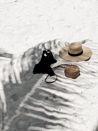 Shadow on sunhat and black top on beach