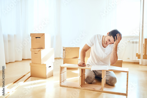 Concentrated young man reading instructions to assemble furniture at home Canvas Print