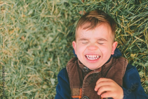 Close up of smiling boy laying on grass