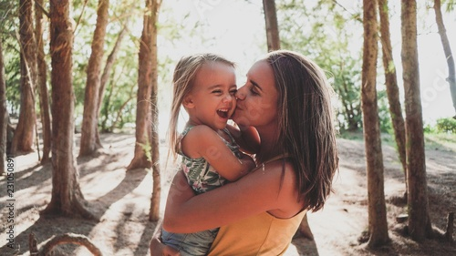 Mother kissing her daughter at outdoors