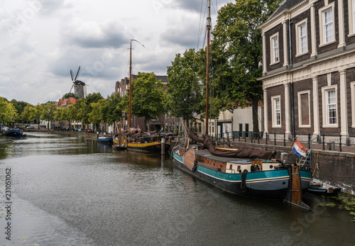 Staande foto Rotterdam Traditional wooden sailing ships in water channel. Old historic harbor of Schiedam, The Netherlands
