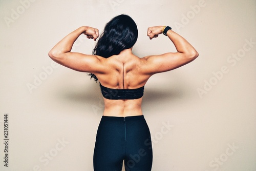 Rear view of young woman flexing muscles against white background