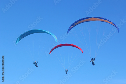 Paragliders in a blue sky