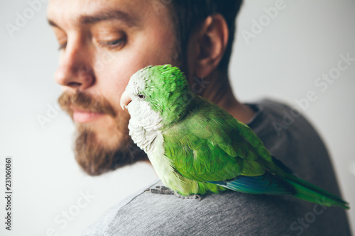 Close-up of beard man with green Quaker sitting on shoulder. Parrot and guy are looking at each other