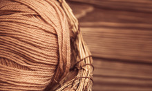Top View Of Brown Woolen Tangles Of Threads In Wicker Basket On Wooden Knitting Background