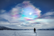 Rear View Of Person Standing On Snowy Landscape Against Colorful Cloudy Sky