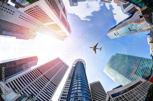 Business Concept With Plane Flying Over Modern Skyscrapers in Singapore