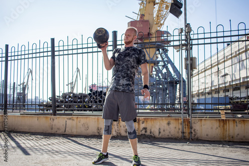Fototapeta Young bearded male athlete training in industrial zone in sunny day, kettlebells exercises outdoors, urban background obraz na płótnie