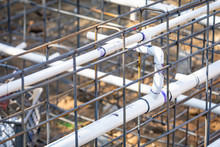 Newly Installed PVC Plumbing Pipes And Steel Rebar Configuration At Construction Site