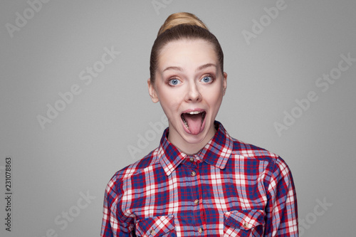 portrait of funny beautiful blonde girl in pink checkered shirt, collected bun hairstyle and makeup standing with open mouth, tongue out and big eyes Wallpaper Mural