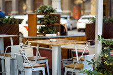 Empty Table In The Summer Terrace Cafe, A Wooden Tabletop And An Iron Leg Against The Background Of Chairs And Shelves With Plants.