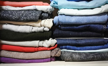 Pants (jeans, Joggers, Drums) Of Different Bright Colors Stacked On A Closet Shelf