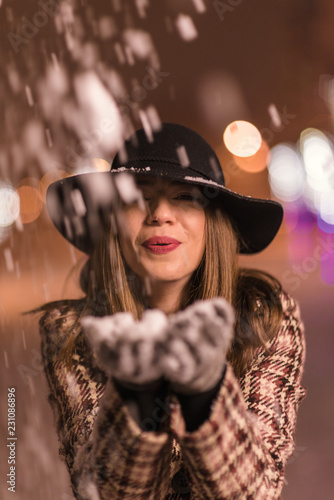 Poster Gypsy Young girl standing in front on christmas tree lights holding snow in her hands and blowing it. girl on christmass alone in the park