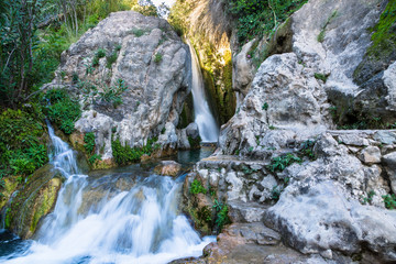 Wonderful waterfall between solid rocks in a natural pond. Fuentes del Algar Costa blanca spain - Alicante Benidorm