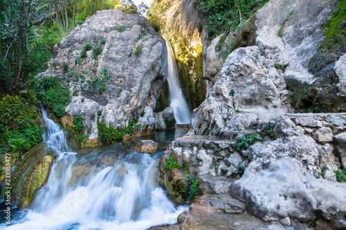 Wonderful waterfall between solid rocks in a natural pond. Fuentes del Algar Costa blanca spain - Alicante Benidorm