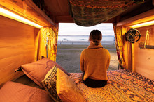Woman Watching Sunset Over Beach From Bohemian Camper Van In A Van Life Theme