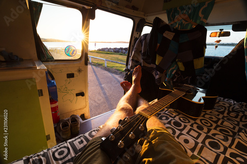 Valokuva Point of view relaxed man in van life camper van theme with guitar and sunset