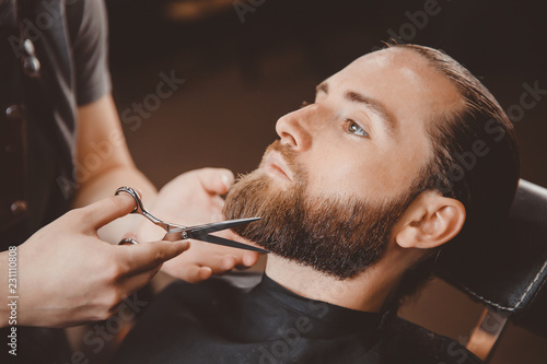 Fototapeta Hipster client man visiting in barber shop shaving beard scissors