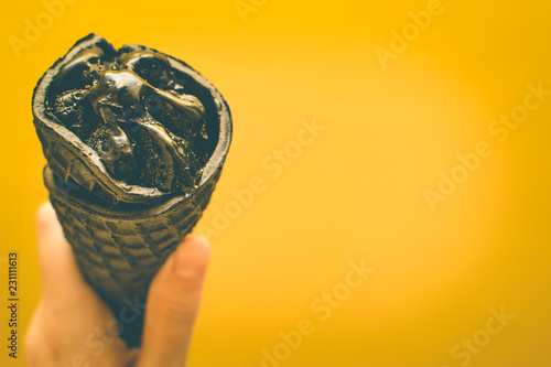 Photo  Black ice cream in a waffle cone on a yellow background in the hand of man