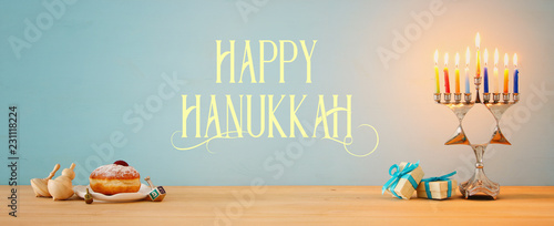Banner of jewish holiday Hanukkah background with traditional spinnig top, menorah (traditional candelabra) and burning candles