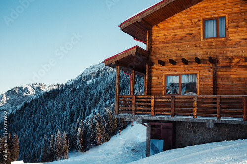 Fotografija Winter vacation holiday alpine wooden house skiing relax leisure resort in the mountains covered with snow and blue sky