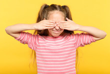 See No Evil. Cute Smiling Girl Covering Eyes With Hands. Portrait On Yellow Background.