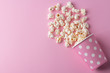 canvas print picture - Spilled popcorn on a pink background, cinema, movies and entertainment concept