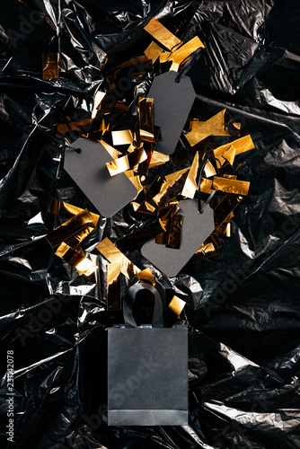Fotografia  top view of paper shopping bag with blank price tags and golden confetti on blac