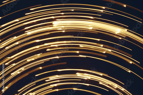 Blurred bright luminous golden stripes in the form of an arc from diode bulbs LED from Christmas lights screen closeup. Bright abstract background ideal for any design