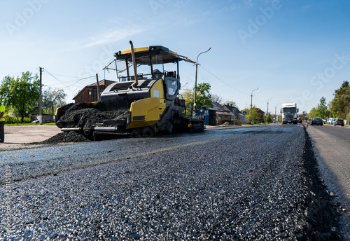 Fototapeta Worker operating asphalt paver machine during road construction and repairing works